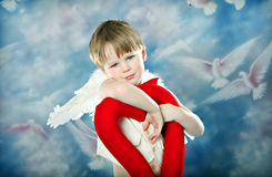 Cupid's Heart. Boy in Cupid costume Holding Red Heart stock images