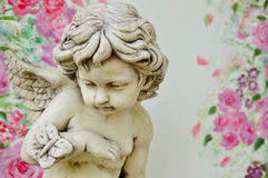 Cupid sculpture. Vintage cupid sculpture with floral background Royalty Free Stock Images