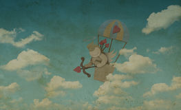 Cupid shoot bow in hot air balloon made from recycled paper on b Stock Image