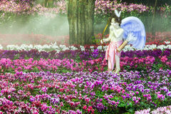Cupid stand on the flower garden. And water spray at night garden royalty free stock photos