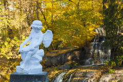 Cupid statue in autumn forest. Autumn forest scene with white statue the in centre Stock Photos