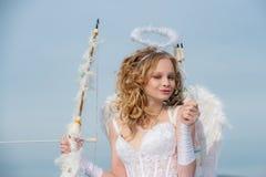 Cupido del d?a de tarjetas del d?a de San Valent?n Muchacha inocente con las alas del ?ngel que se oponen con el arco y la flecha imagen de archivo
