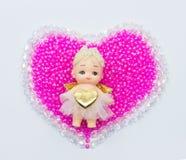 Cupido sul centro sui cuori del biglietto di S. Valentino delle perle e del cristallo Immagini Stock