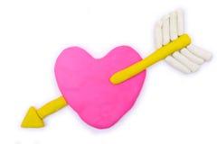 Cupidon et argile rose de pâte à modeler de forme de coeur Photographie stock libre de droits