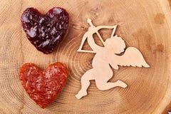 Cupidon près de pain en forme de coeur de gelée Photographie stock