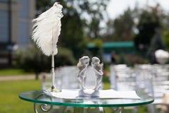 Cupidos, certificado del andde la pluma en la tabla para el registro de la boda Fotos de archivo