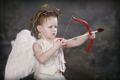Cupids Arrow. Boy in Cupid costume shooting bow and arrow royalty free stock photos