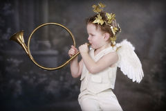 Cupids Golden Horn. Boy in Cupid costume playing a beautiful golden horn stock photo