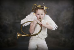 Cupids Golden Horn. Boy in Cupid costume playing a beautiful golden horn royalty free stock photos