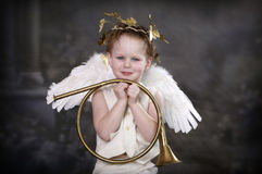 Cupids Perfect Pose. Boy in Cupid costume holding a beautiful golden horn stock photo