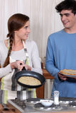 Cuple making crepes. Stock Photo