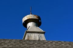 Cupola on a barn with bullet holes. A metal cupola on the roof line of a shingled barn is riddled with bullet holes Stock Photos