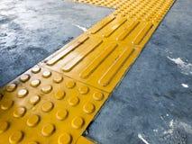 Cupola e blocco gialli di pavimentazione tattile che fungono da orientamento affinchè il cittadino cieco o cieco evitino il risch immagine stock libera da diritti