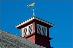 Cupola with a wind vane of a trotting horse. A cupola on a ranch stable barn displays a weather vane with a horse trotting royalty free stock images