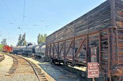 Vintage Caboose, Tanker Cars, & Cattle Car. The cupola style caboose, tanker cars, and cattle car all belong to a bygone era of railroading. The side on the royalty free stock image