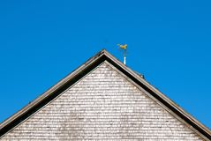 Cupola with a wind vane of a trotting horse. The back end of a ranch stable barn displays a weather vane with a horse trotting stock images