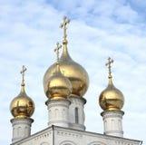 Cupole dell'oro della chiesa ortodossa russa sui precedenti di cielo blu La Russia siberia immagine stock