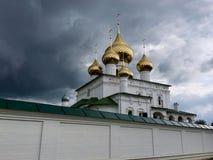Cupole dorate della chiesa ortodossa e le pareti bianche del tempio contro lo sfondo di un cielo grigio tempestoso fotografia stock