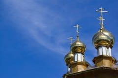 Cupole ed incroci dorati della chiesa ortodossa russa sul fondo del cielo blu immagini stock