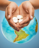 Cupped hands holding euro coins over earth globe Royalty Free Stock Image