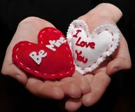 Cupped hands holding two hearts. A girl`s hands holding two hearts, one saying `Be Mine` and the other one `I Love You` the hands are  on a black background Stock Image