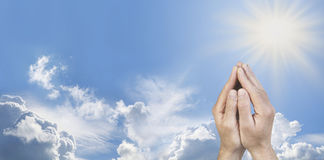 Cupped Hands in Prayer Position on Blue Sky