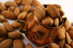 Cupper Bowl and Almonds. Almonds in a cuppur cup and some other on white surface royalty free stock photo
