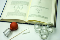 Cupping glasses with textbook. For studying Stock Photo