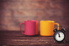 Cups and alarm clock Stock Photos