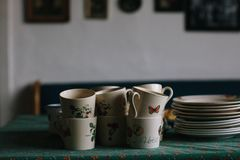 Cups awaiting the coffee-drinkers. Some cups and plates placed on the kitchen table ready for the guests to arrive in the wintertime royalty free stock image