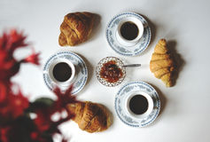 Cups of black coffee, croissants and jam Stock Images