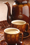 Cups of cappuccino and coffee pot Royalty Free Stock Image
