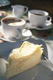 Cups of coffe with cheesecake. Cups of coffee and cappuccino with baked lemon cheesecake, served on a square plate. Shallow depth of field. Cheesecake is in Royalty Free Stock Photos
