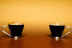 Cups of coffee. Two glass cups of coffee against a warm background with copy space Stock Images