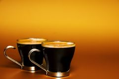 Cups of coffee. Two glass cups of coffee against a warm background with copy space Royalty Free Stock Photos