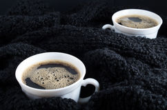 Cups of coffee on a background of black wool scarf Royalty Free Stock Images