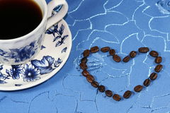 Cups of coffee with beans in blue background Royalty Free Stock Photography
