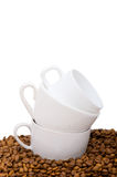 Cups and coffee beans isolated on the  white. Cups and coffee  beans isolated on the white Stock Image