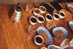 Cups of coffee, beans, and kettle on table for tasting. High angle view of a wooden table with many cups of coffee, fresh roasted beans in open continers, water Stock Photo