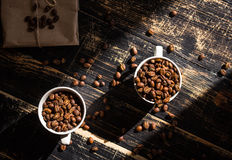 Cups with coffee beans at morning sunlight Stock Photos