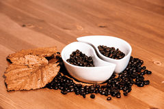 Cups with coffee beans on a wooden table Stock Photo