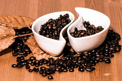 Cups with coffee beans on a wooden table Royalty Free Stock Image