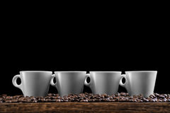 Cups of coffee with coffee beans isolated on black background, product photography for coffee shop Royalty Free Stock Photos
