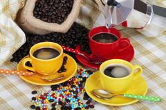 Cups of coffee with a coffee maker. Jute sack and coffee grains and cups and colored sugar pearls and a coffee maker on colored cloth as background Stock Photos