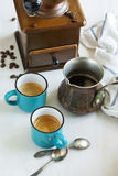 Cups of coffee, coffee pot and coffee grinder. Stock Photos