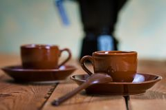 Cups of coffee and a coffee pot on a table Royalty Free Stock Photography