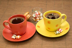 Cups of coffee with colorful candies and glass bowl between them. Yellow and orange cup of coffee with colorful candies and glass bowl between them on wooden rug royalty free stock photos