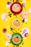 Cups of Coffee and colorful paper circles on yellow paper background. Flat lay stock images
