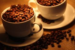 Cups of coffee, full of beans. Royalty Free Stock Photo