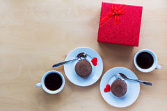 Cups with coffee, gift box and coockies on wooden table. Stock Images